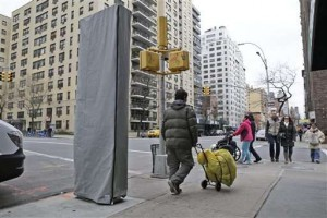 In this photo taken on Thursday, Dec. 31, 2015, people walk near a covered wireless kiosk at an intersection in New York. The 9-foot-tall, narrow structure installed this past week on a Manhattan sidewalk is signaling a plan to turn payphones into what's billed as the world's biggest and fastest municipal Wi-Fi network. The first of at least 7,500 planned hot spots are due to go online early next year, promising superfast and free Wi-Fi service, new street phones with free calling, ports to charge personal phones and a no-cost windfall for the city. (AP Photo/Seth Wenig)